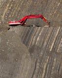 在石头坑的红色挖掘者 免版税库存照片