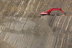 在石头坑的红色挖掘者 免版税库存图片