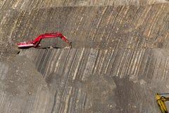 在石头坑的红色挖掘者 图库摄影