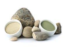 在石头旁边的白色和绿色化妆黏土在一白色backg 免版税库存照片