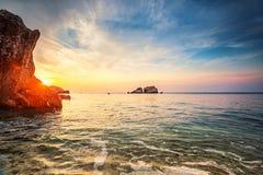 在石头海滩的热带五颜六色的日落 库存照片