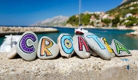 在石头绘的克罗地亚名字,小船在小游艇船坞在背景中 库存图片