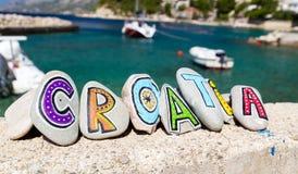 在石头绘的克罗地亚题字,小船在背景中 免版税库存图片