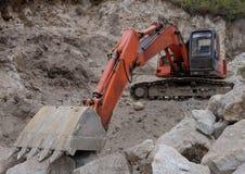在石头的挖掘机 库存照片