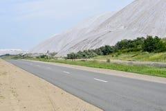 在矿边缘白俄罗斯,市的转储的柏油路Soligorsk 免版税库存照片