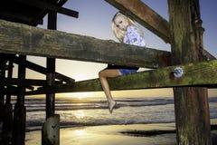 在码头下的白肤金发的女孩 免版税库存照片