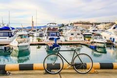 在码头停放的自行车 汽船和豪华游艇在海港靠了码头 城市街道和大海 暑假假期 库存照片
