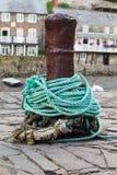 在码头区的一个老生锈的系船柱 免版税库存图片