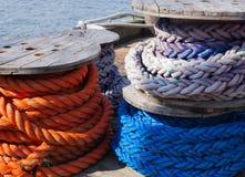 在码头堆积的五颜六色的船舶绳索短管轴  免版税库存图片