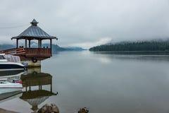 在码头有眺望台的和雾的快速汽艇在捷列茨科耶湖,阿尔泰,俄罗斯 库存照片