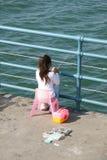在码头的女孩渔 免版税图库摄影