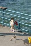在码头的女孩渔 免版税库存图片