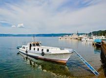 在码头的小船在清楚的绿松石的贝加尔湖浇灌 图库摄影