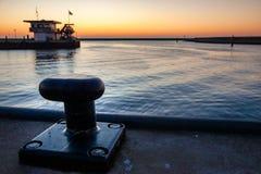 在码头的系船柱在一个落日期间 图库摄影