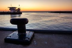 在码头的系船柱在一个落日期间 免版税库存照片