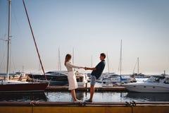 在码头的逗人喜爱的年轻美好的夫妇在与小游艇的口岸,行家,愉快的微笑的室外画象 图库摄影