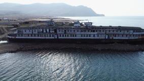 在码头的Od白色和黑大船身分在反对山小山和天空蔚蓝的海水附近 ?? 股票视频