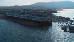 在码头的Od白色和黑大船身分在反对山小山和天空蔚蓝的海水附近 ?? 图库摄影