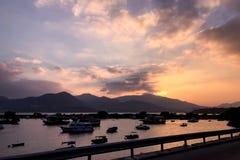 在码头和梯度橙色天空的渔船在日落 免版税图库摄影