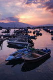 在码头和梯度橙色天空的渔船在日落 免版税库存照片