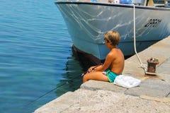 在码头的小男孩渔在被停泊的小船附近 elba海岛 免版税库存图片