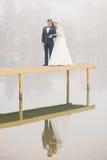 在码头的新郎和新娘立场在水中被反射 免版税库存照片