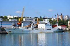 在码头的生锈的白色船 免版税库存图片