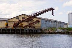 在码头的老起重机 免版税库存照片