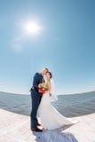 在码头的年轻婚礼夫妇 免版税库存图片