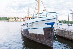 在码头附近的一条白色老木小船 库存照片