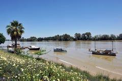在码头,瓜达尔基维尔河河,它穿过真皮del里约,塞维利亚省,安大路西亚,西班牙的小船 库存图片