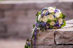 在砂岩墙壁上的婚礼花束 库存照片