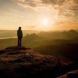 在砂岩岩石的锋利的角落的远足者立场在岩石帝国停放和观看在有薄雾和有雾的早晨谷对太阳 库存照片