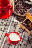 在研磨机的新鲜的牛奶和碾碎的咖啡 免版税库存图片