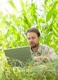在研究便携式计算机的麦地前面的农夫 免版税库存照片