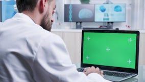 在研究绿色屏幕膝上型计算机的实习者肩膀射击的移动式摄影车 影视素材
