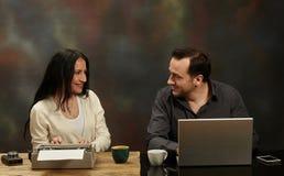 在研究膝上型计算机的打字机和一个人的妇女文字 teched的 免版税库存照片