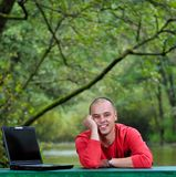 在研究膝上型计算机的红色衬衣的新生意人 免版税库存照片