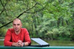 在研究膝上型计算机的红色衬衣的新生意人 免版税图库摄影