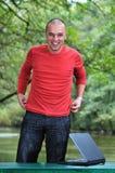 在研究膝上型计算机的红色衬衣的新生意人 免版税库存图片