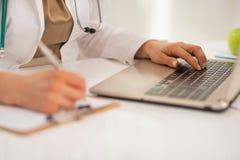在研究膝上型计算机的医生妇女的特写镜头 免版税库存图片