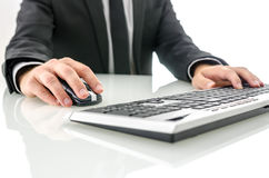 在研究计算机的办公桌的商人 免版税库存图片