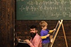 在研究计算机的黑板的学生图画和老师或者父亲 紧接坐与站立的侧视图人 免版税库存照片