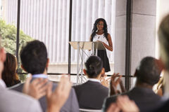 在研讨会的观众赞许年轻黑人妇女的在讲演台 库存图片