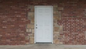 在砖和石墙的难看的东西白色门 库存图片