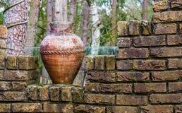 在砖墙、室外庭院装饰和建筑学上的老切削的罗马花瓶 免版税库存照片