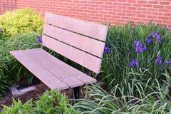 在砖墙、花和植物中的公园长椅 免版税库存图片