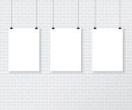 在砖墙上的三白色海报 免版税库存图片