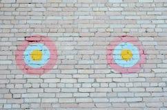 在砖墙上的两个装饰红蓝色黄色圈子 免版税库存图片