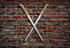 在砖墙上的两把剑 免版税库存照片